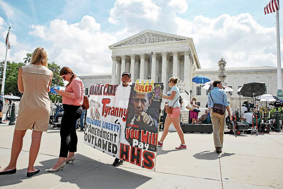 (AP Photo/J. Scott Applewhite) Protestors, press and passersby wait for decisions in the final days of the Supreme Court's term, in Washington on June 25, 2014. The Hobby Lobby chain of arts-and-crafts stores does not want to provide insurance coverage for certain forms of contraception that it finds objectionable on religious grounds. Photo: AP / AP