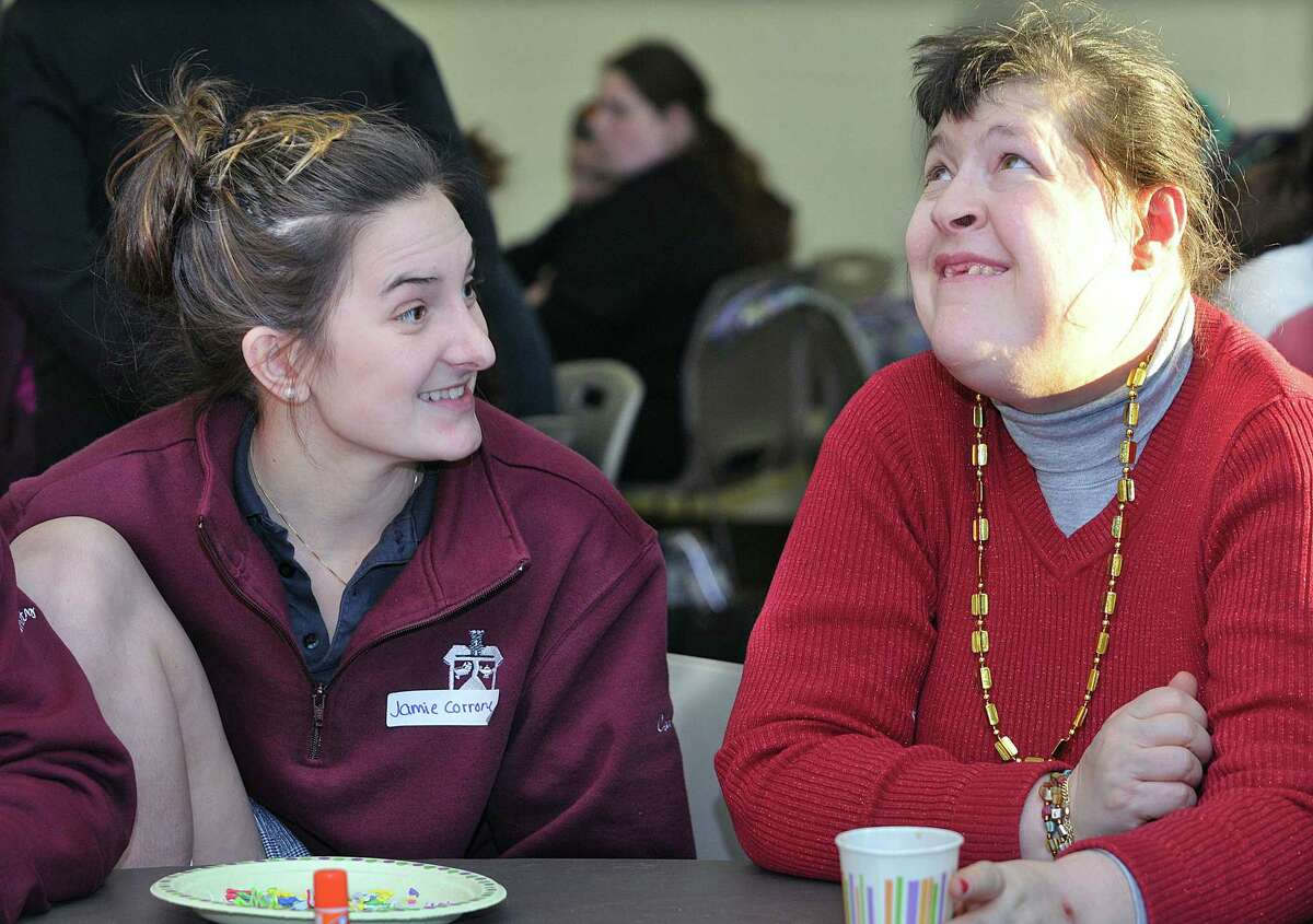 Mercy High School senior Jamie Corrone talks with Sandy Fazzino while working on an art project Thursday afternoon during the MYARC Arts & Crafts program in the school cafeteria in Middletown. Corrone is in her fourth year as MYARC volunteers.