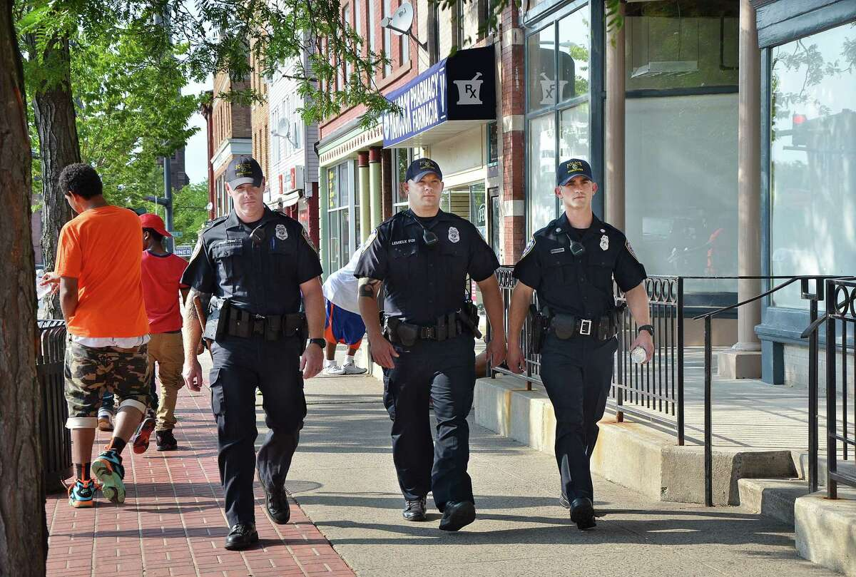 Catherine Avalone-The Middletown Press Officers Nate Peck, Mark Lamieux and Jesse Santostefano, left to right, of the Middletown Police Department patrol Main Street Monday afternoon.