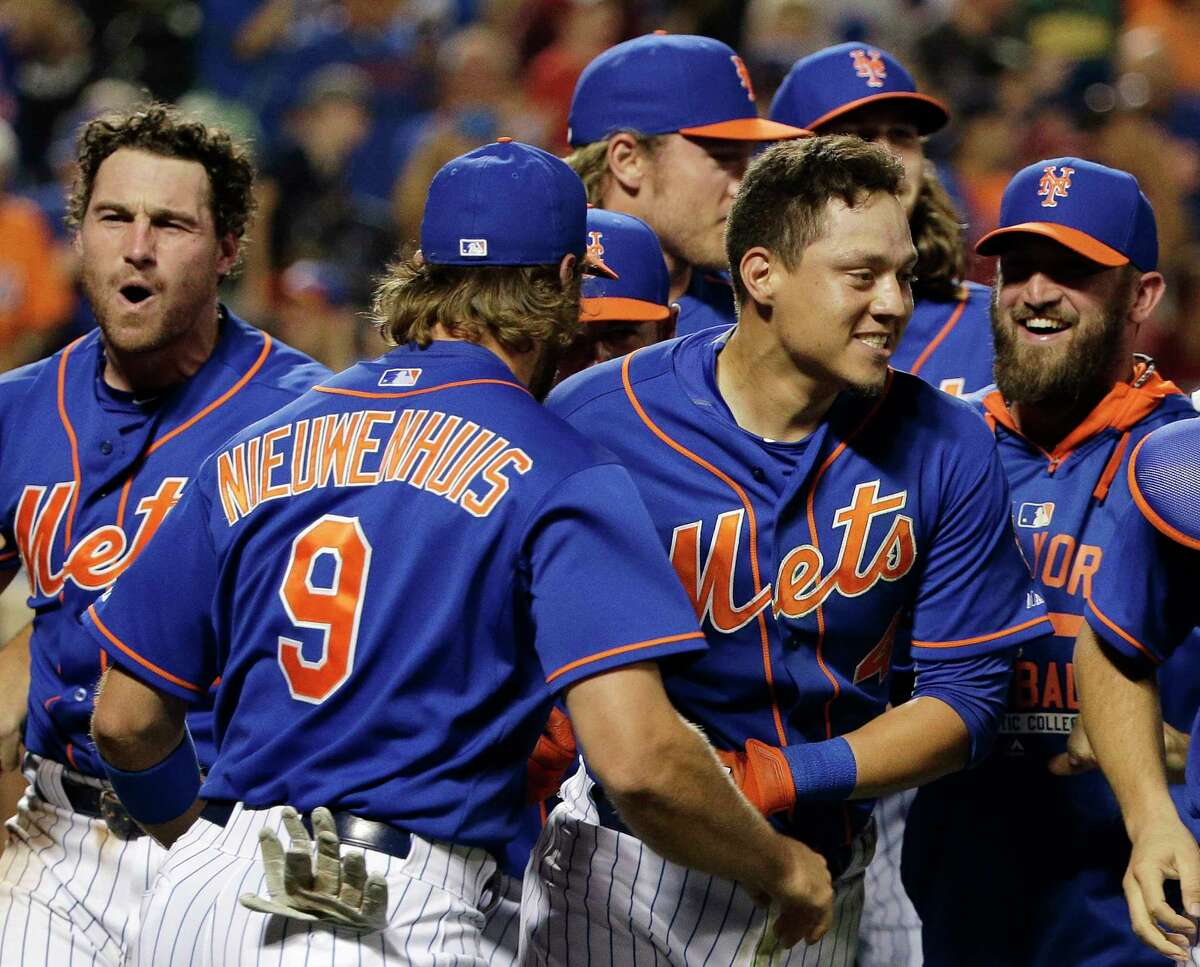 In this file photo from July 31, the Mets' Wilmer Flores, center right, is mobbed by teammates after hitting a walk-off solo home run during the 12th inning to beat the Nationals just two days after Flores thought he had been traded.