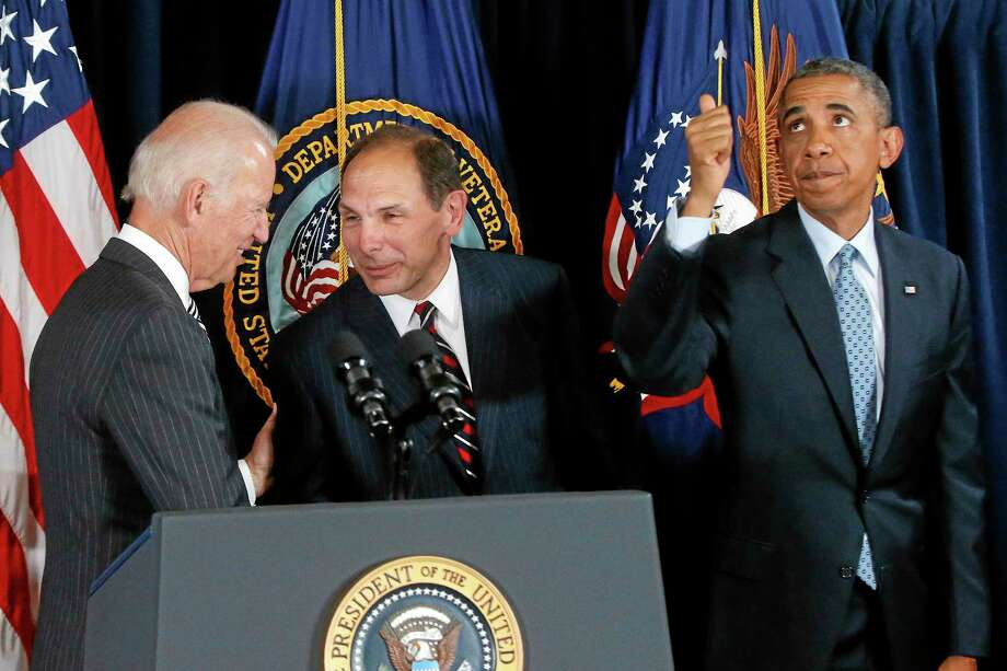 President Barack Obama givers a thumbs up to audience members seated above as he nominates former Procter and Gamble executive Robert McDonald, center, as the next Veterans Affairs secretary at the Department of Veterans Affairs in Washington, Monday, June 30, 2014. Vice President Joe Biden is at left. If confirmed by the Senate, McDonald would succeed Eric Shinseki, the retired four-star general who resigned last month as the scope of the issues at veterans' hospitals became apparent. (AP Photo/Charles Dharapak) Photo: AP / AP
