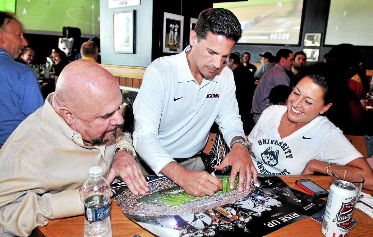 UConn football coach Bob Diaco, center, signs a poster for Michael Jelormine, left, of Southport and his daughter Kristen of Stratford at Buffalo Wild Wings in Milford.