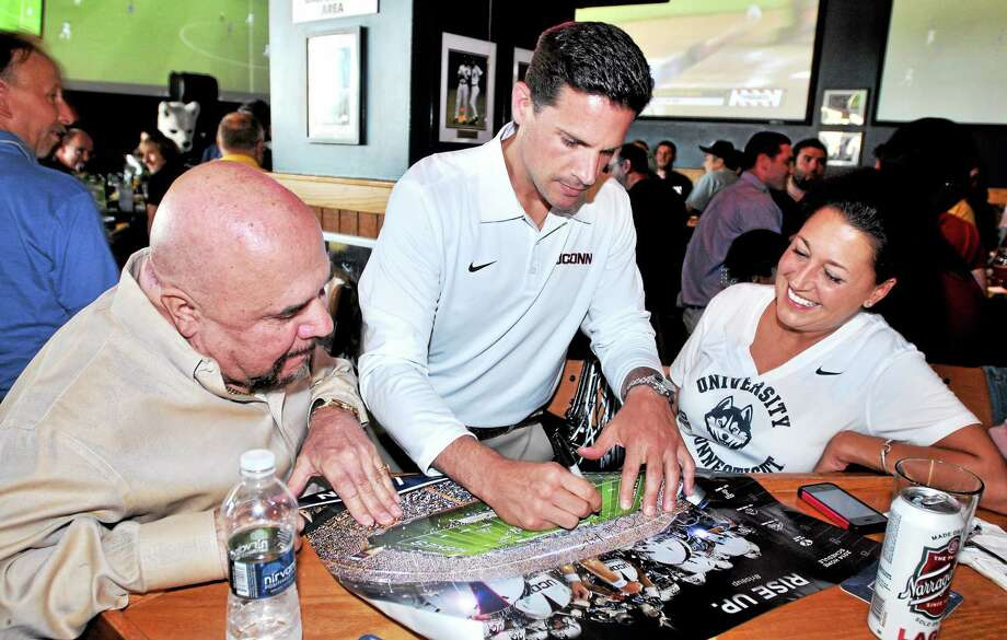 UConn football coach Bob Diaco, center, signs a poster for Michael Jelormine, left, of Southport and his daughter Kristen of Stratford at Buffalo Wild Wings in Milford. Photo: Arnold Gold — Register