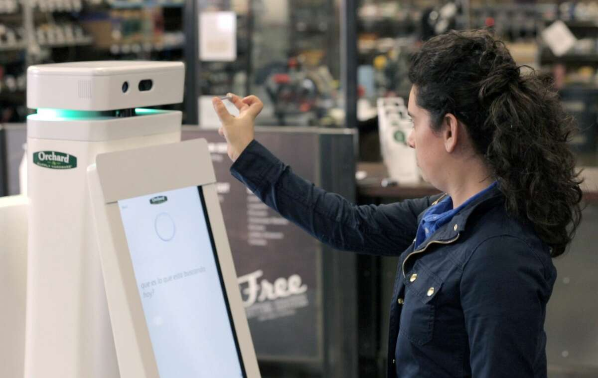 In this undated image provided by Lowe's, a woman holds a nail up to be scanned by an OSHbot robot. The robots are equipped with 3D cameras so they can scan and identify items.