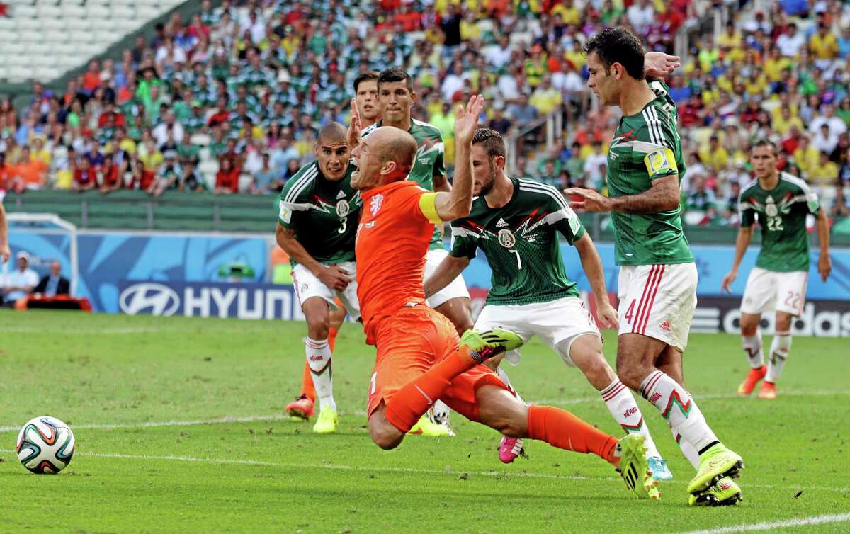 The Netherlands' Arjen Robben, center, goes down to earn a penalty during Sunday's match against Mexico.