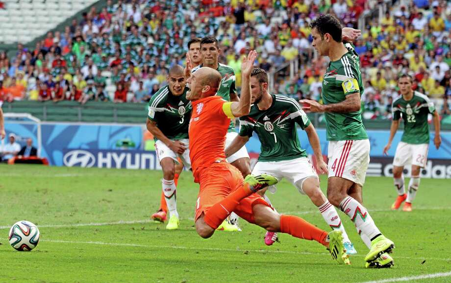 The Netherlands' Arjen Robben, center, goes down to earn a penalty during Sunday's match against Mexico. Photo: Wong Maye-E — The Associated Press  / AP