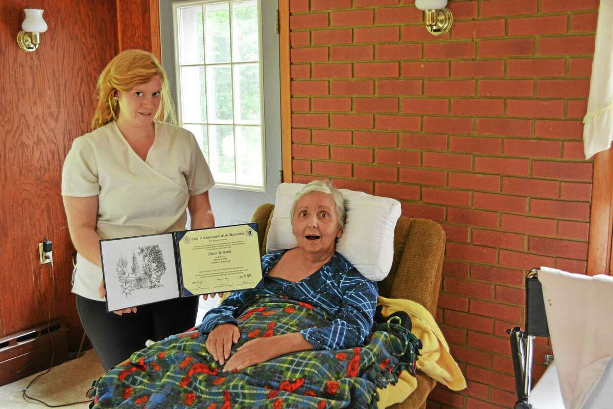 Kayla Brown, Maria Swift's caregiver, holds the hard-earned diploma for the Cromwell resident who just earned her master's degree, completing coursework by using an eye-gaze computer.