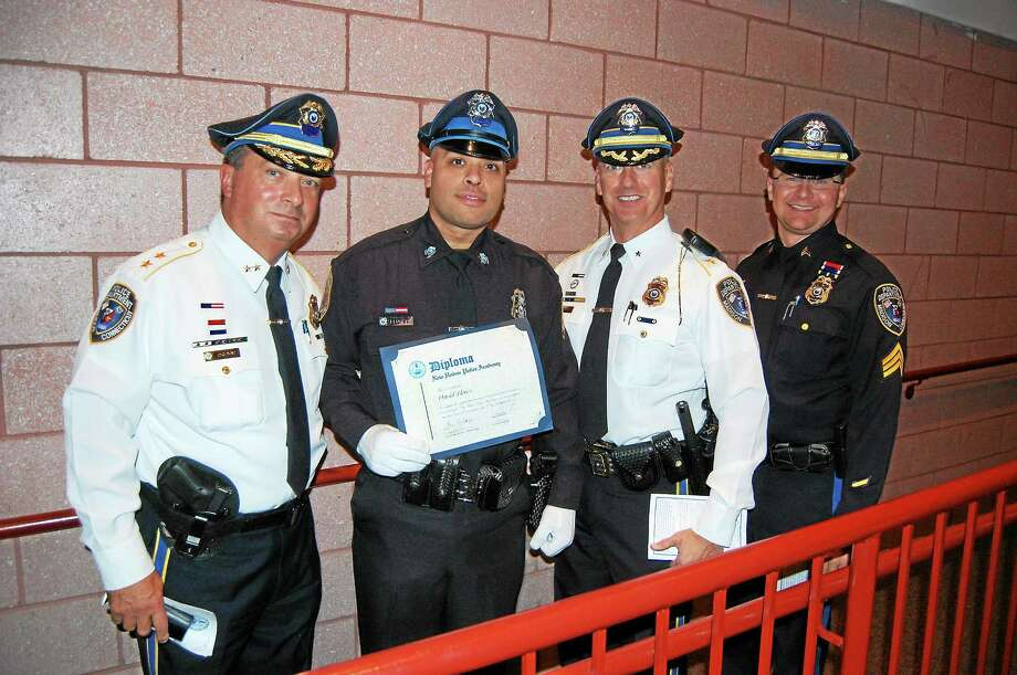 Pictured from left to right: Chief Jack Drumm, Officer David Flores, Commander John Rich and Sgt. Joseph Race. Flores recently graduated from the New Haven Police Academy and joined the Madison Police Department as the first Hispanic officer. Photo:  Courtesy Of The Madison Police Department