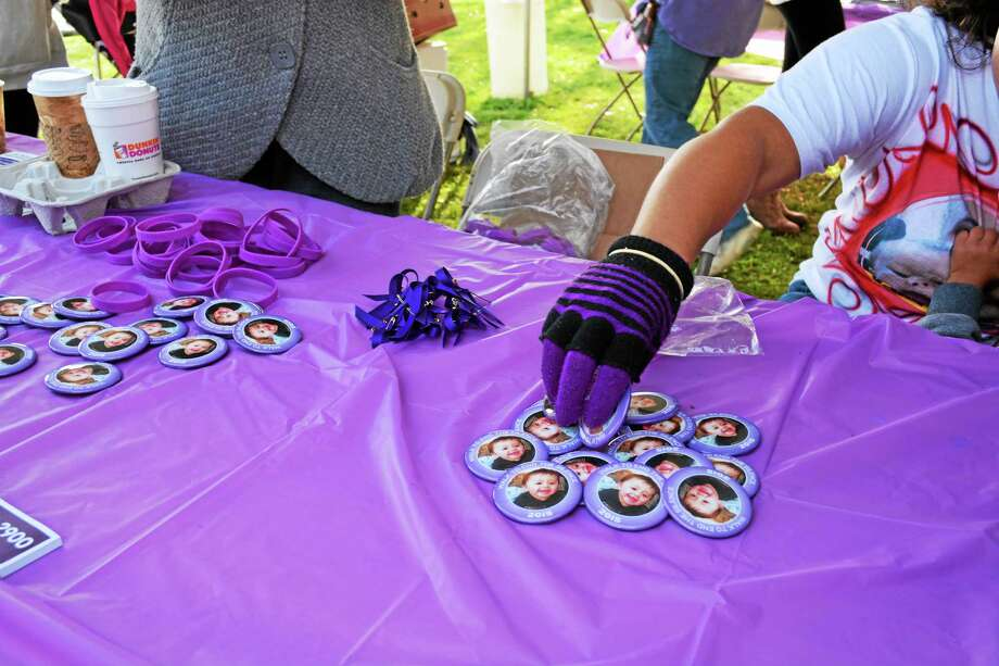 Purple bracelets and ribbons signifying Domestic Violence Awareness Month, along with pamphlets and buttons bearing Aaden Moreno's photograph were handed out at the event. Photo: Journal Register Co.