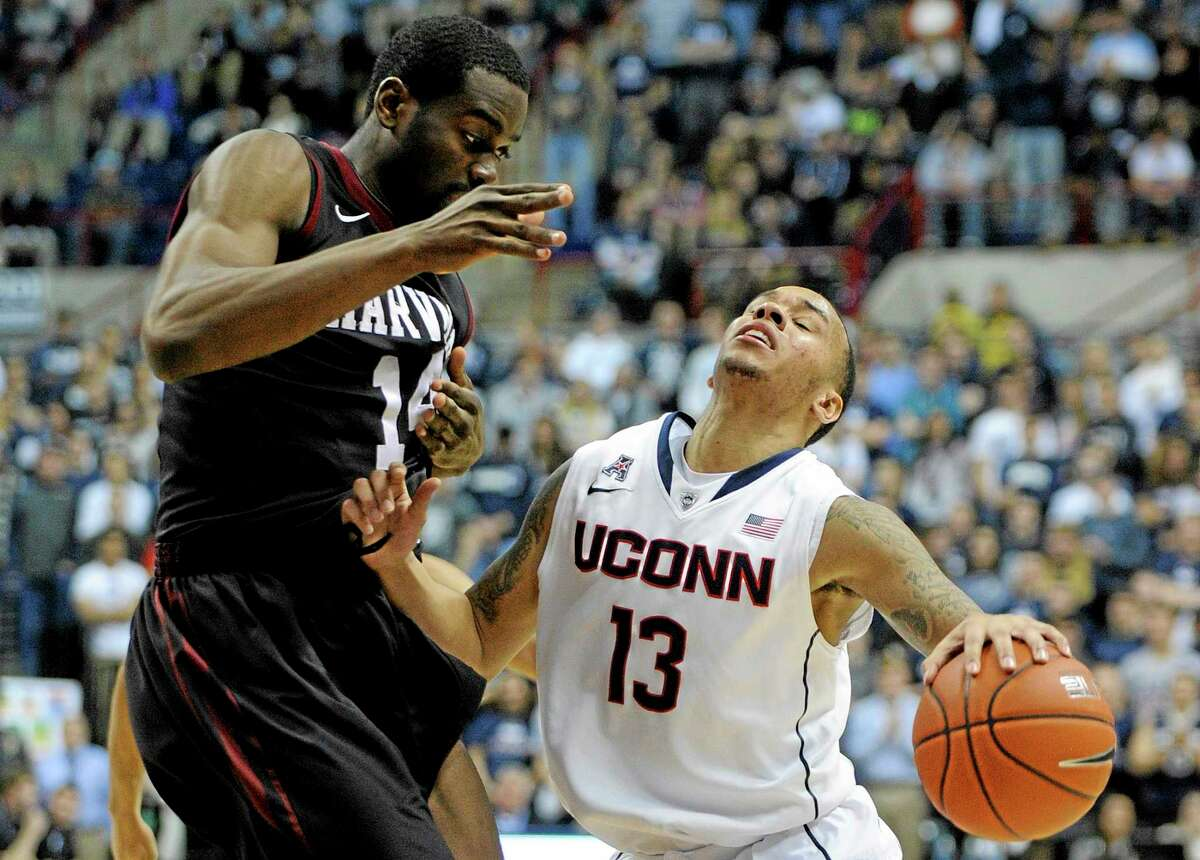 UConn's Shabazz Napier (13) drives past Harvard's Steve Moundou-Missi (14) during the second half of Connecticut's 61-56 victory.