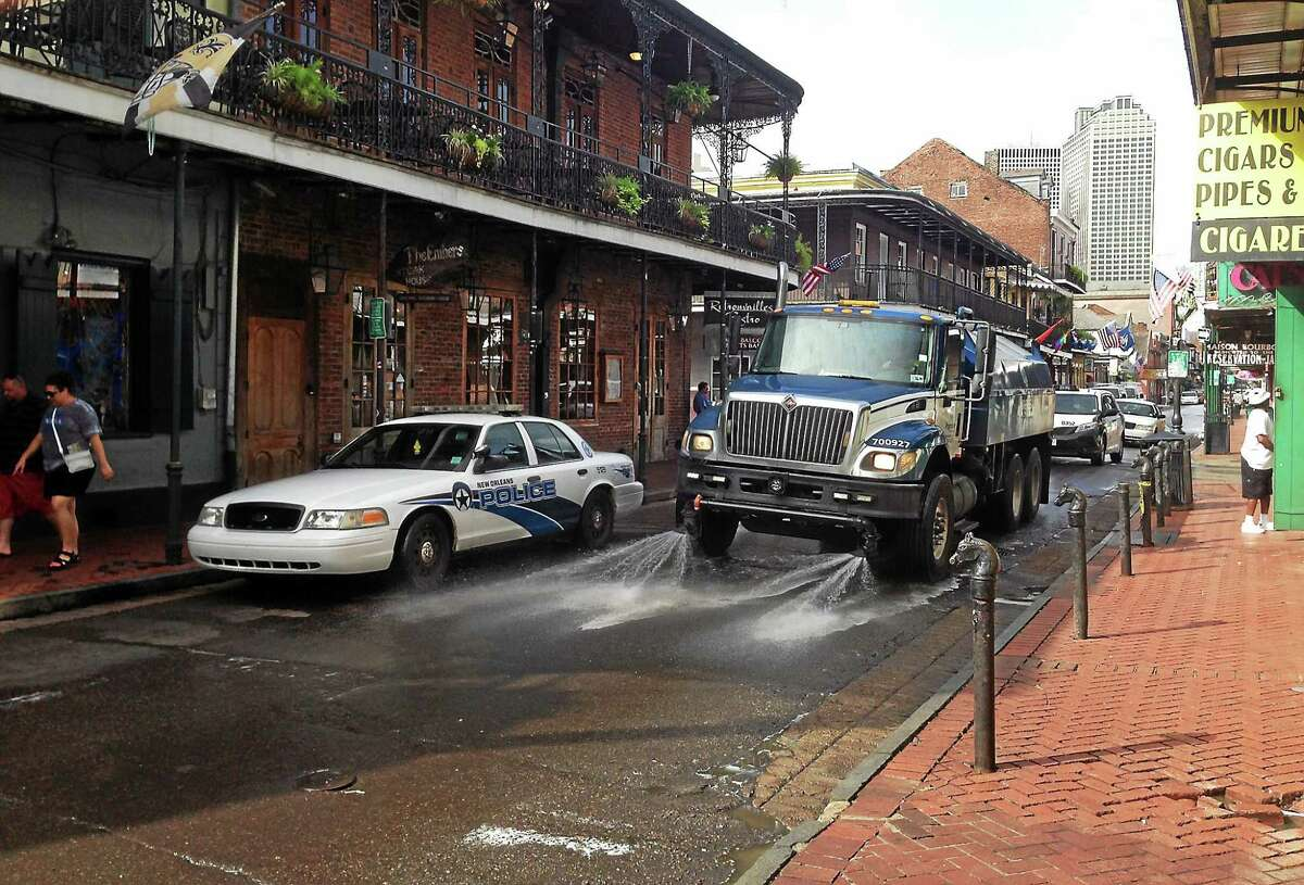 A Progressive Waste Solutions truck sprays along Bourbon Street, following a shooting earlier in the day on June 29, 2014, in New Orleans.