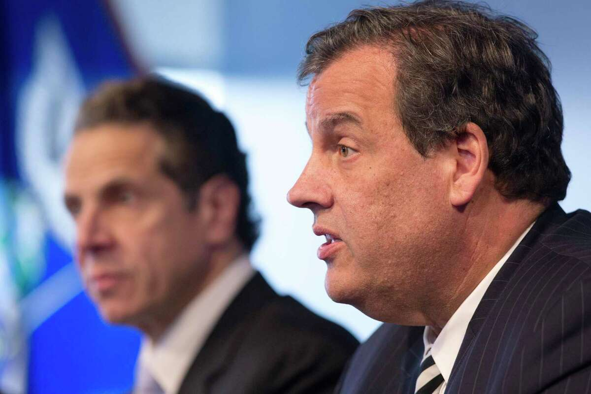 New York Governor Andrew Cuomo, left, listens as New Jersey Governor Chris Christie talks at a news conference on Oct. 24, 2014 in New York.