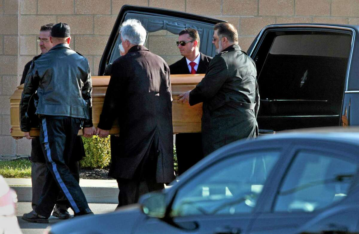FILE - In this Dec. 18, 2013, file photo, the casket of Dustin Friedland is carried into a temple for a funeral service in Lakewood, N.J. Four men charged in the fatal carjacking of the young lawyer at an upscale New Jersey mall just before Christmas were due in court Wednesday for arraignment.