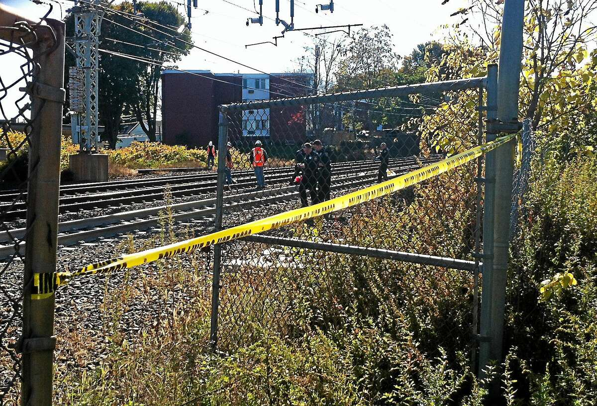 Investigators from Amtrak and the Metropolitan Transit Authority collect evidence Monday afternoon from the train tracks just west of the Milford Metro-North station. MTA officials said a female trespasser was fatally struck by an Amtrak train.