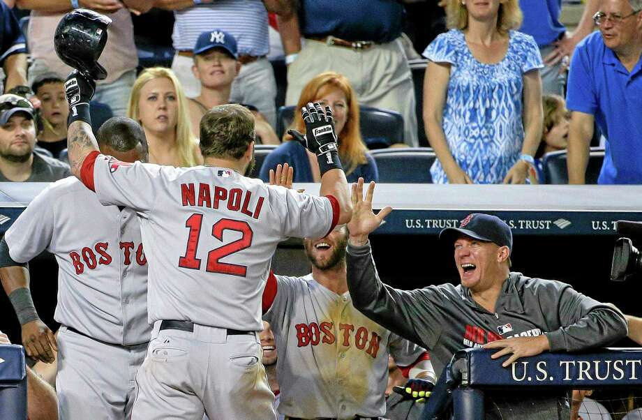 Mike Napoli is greeted by coaches and teammates after hitting a solo home run in the ninth inning Saturday. Photo: Julie Jacobson — The Associated Press  / AP