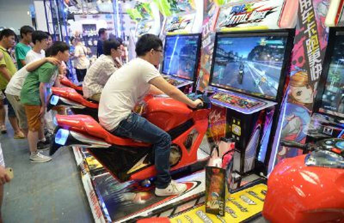 Visitors play video games on the opening day of the 9th China International Comics Games Expo (CCG Expo) in Shanghai on July 11, 2013.