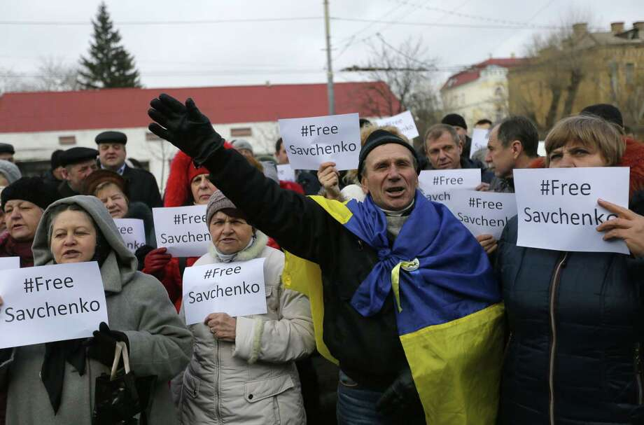 People shout slogans in support of Ukrainian pilot Nadezhda Savchenko during a rally outside the Russian Embassy in Kiev, Ukraine, Tuesday, Feb. 24, 2015.  Ukrainian pilot Nadezhda Savchenko was captured by Russia-backed rebels during fighting in eastern Ukraine. The Kiev government has so far been unsuccessful in seeking the extradition of Savchenko who was elected a member of the Ukrainian parliament in the October 2014 Ukrainian parliamentary election. (AP Photo/Sergei Chuzavkov) Photo: AP / AP