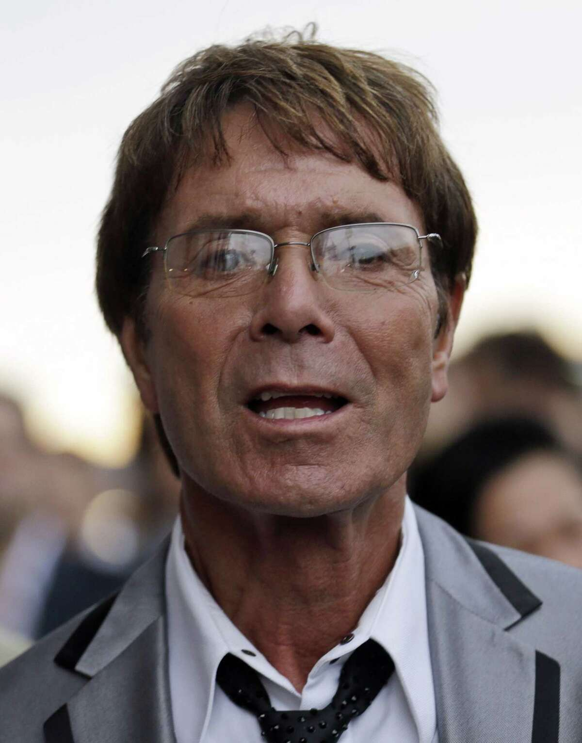 FILE - In this Friday July 27, 2012 file photo, British singer Cliff Richard arrives for the opening ceremony at the 2012 Summer Olympics, in London. A police investigation of veteran pop star Cliff Richard relating to claims of sexual assault has ìincreased significantly in size,î a British lawmaker said Wednesday Feb. 25, 2015. (AP Photo/Markus Schreiber, File)