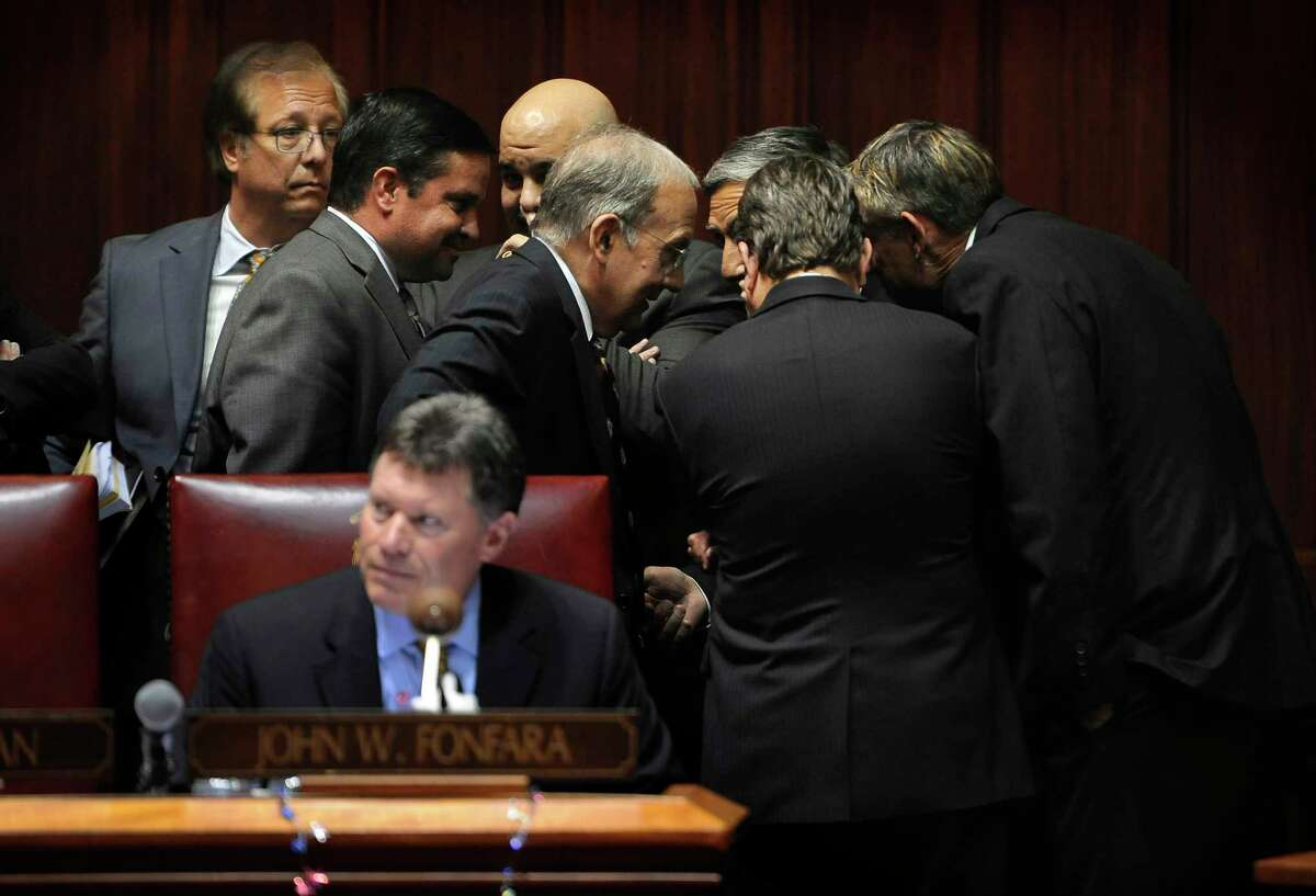 Connecticut Senate Minority Leader Len Fasano, center right, R-North Haven, talks with State Senate President Martin Looney, center left, D-New Haven, in a huddle with other legislators in the Senate Chambers at Capitol on the final day of session on June 3, 2015 in Hartford, Conn.