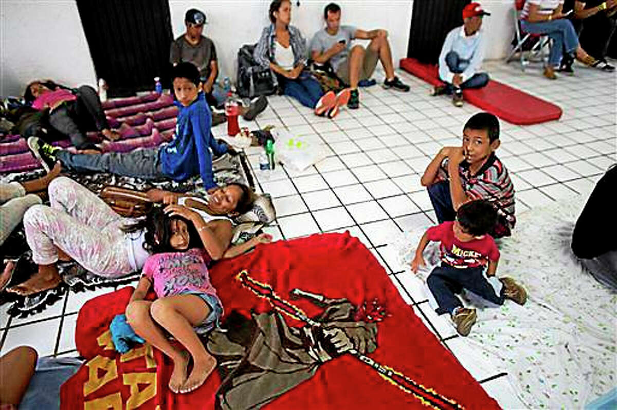 """Residents and tourists take refuge in a small shelter as they await the arrival of Hurricane Patricia in Puerto Vallarta, Mexico, Friday, Oct. 23, 2015. Residents and tourists were hunkering down or trying to make last-minute escapes ahead of what forecasters called a """"potentially catastrophic landfall"""" later in the day."""