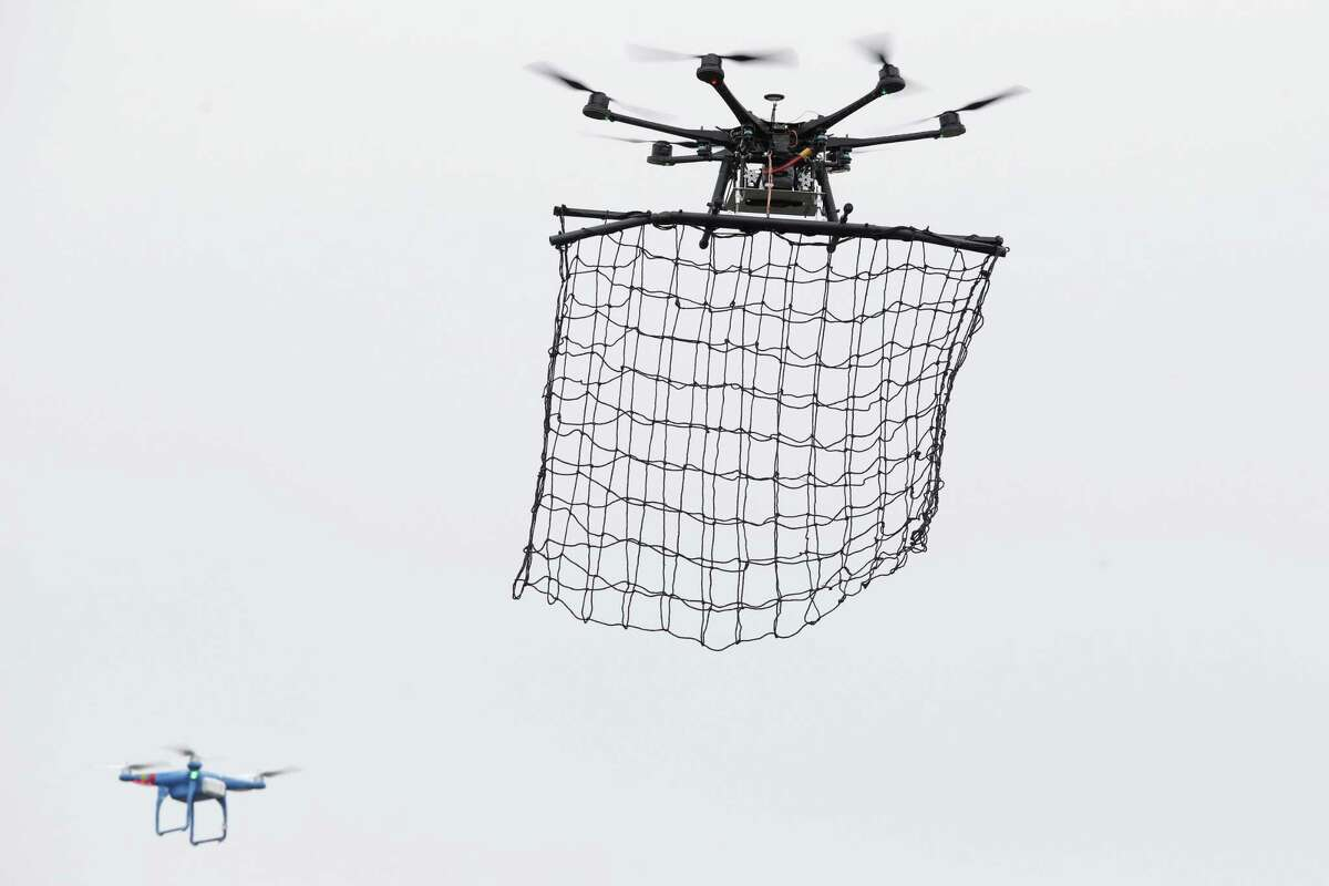 FILE - In this Monday Feb. 9, 2015 file photo, a drone Interceptor MP200, top, prepares to catch a drone DJI Phantom 2 with a net during a demonstration flight in La Queue-en-Brie, east of Paris, France. Paris police say they spotted at least five drones flying over the French capital overnight Tuesday Feb. 24, 2015, and an investigation is under way into who was flying them and why. Franceís BFM television reported that they were seen flying over the Eiffel Tower, the Louvre Museum and the American Embassy, among other locations. (AP Photo/Francois Mori, File)