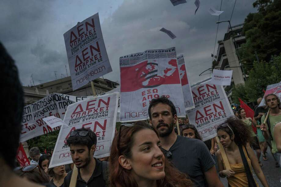 Members of left wing parties hold placards read in Greek 'There is no future in the European Union' during a protest in Athens on Sunday, June 28, 2015. Greek Prime Minister Alexis Tsipras says the Bank of Greece has recommended that banks remain closed and restrictions be imposed on transactions, after the European Central Bank didn't increase the amount of emergency liquidity the lenders can access from the central bank. Photo: AP Photo/Daniel Ochoa De Olza  / AP