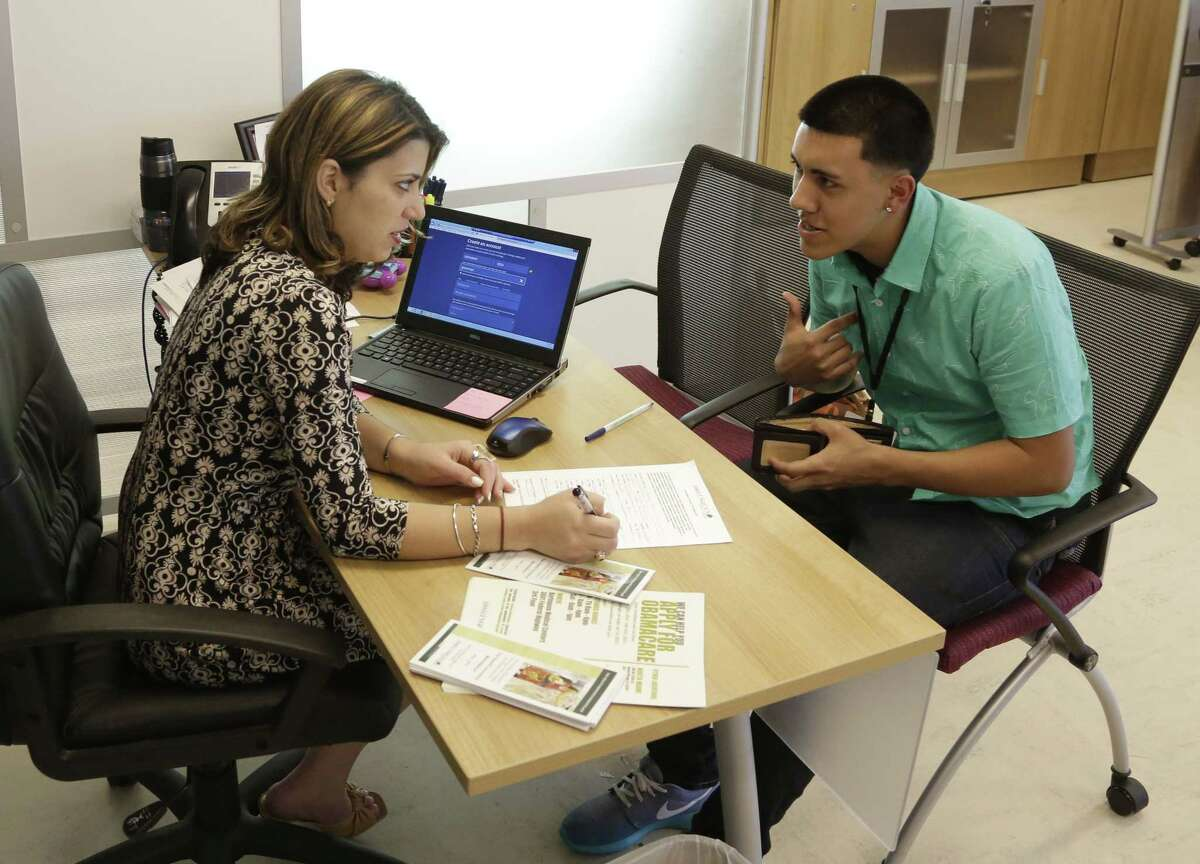 In this Nov. 17, 2014, file photo, navigator Dianelys Dominguez, left, assists Giovanny Vega, 18, of Miami, right, sign up for health insurance under the Affordable Care Act at the Borinquen Medical Center in Miami.