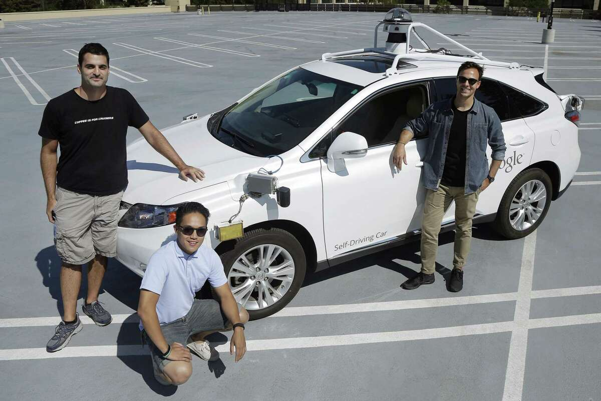 Brian Torcellini, Google team leader of driving operations, right, poses for photos with vehicle safety specialists Rob Miller, top left, and Ryan Espinosa, next to a vehicle at a Google office in Mountain View, Calif.