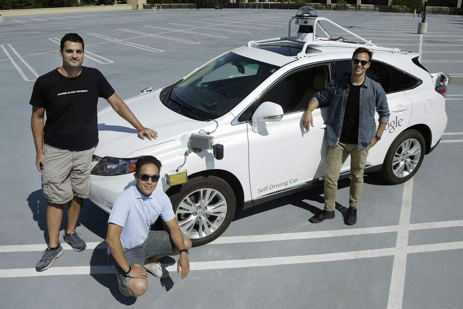 Brian Torcellini, Google team leader of driving operations, right, poses for photos with vehicle safety specialists Rob Miller, top left, and Ryan Espinosa, next to a vehicle at a Google office in Mountain View, Calif. Photo: Jeff Chiu — The Associated Press  / AP