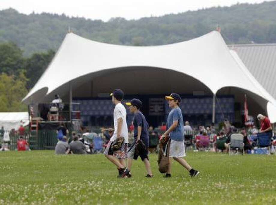 Fans wait for the start of the Baseball Hall of Fame induction ceremony on Sunday, July 28, 2013, in Cooperstown, N.Y.