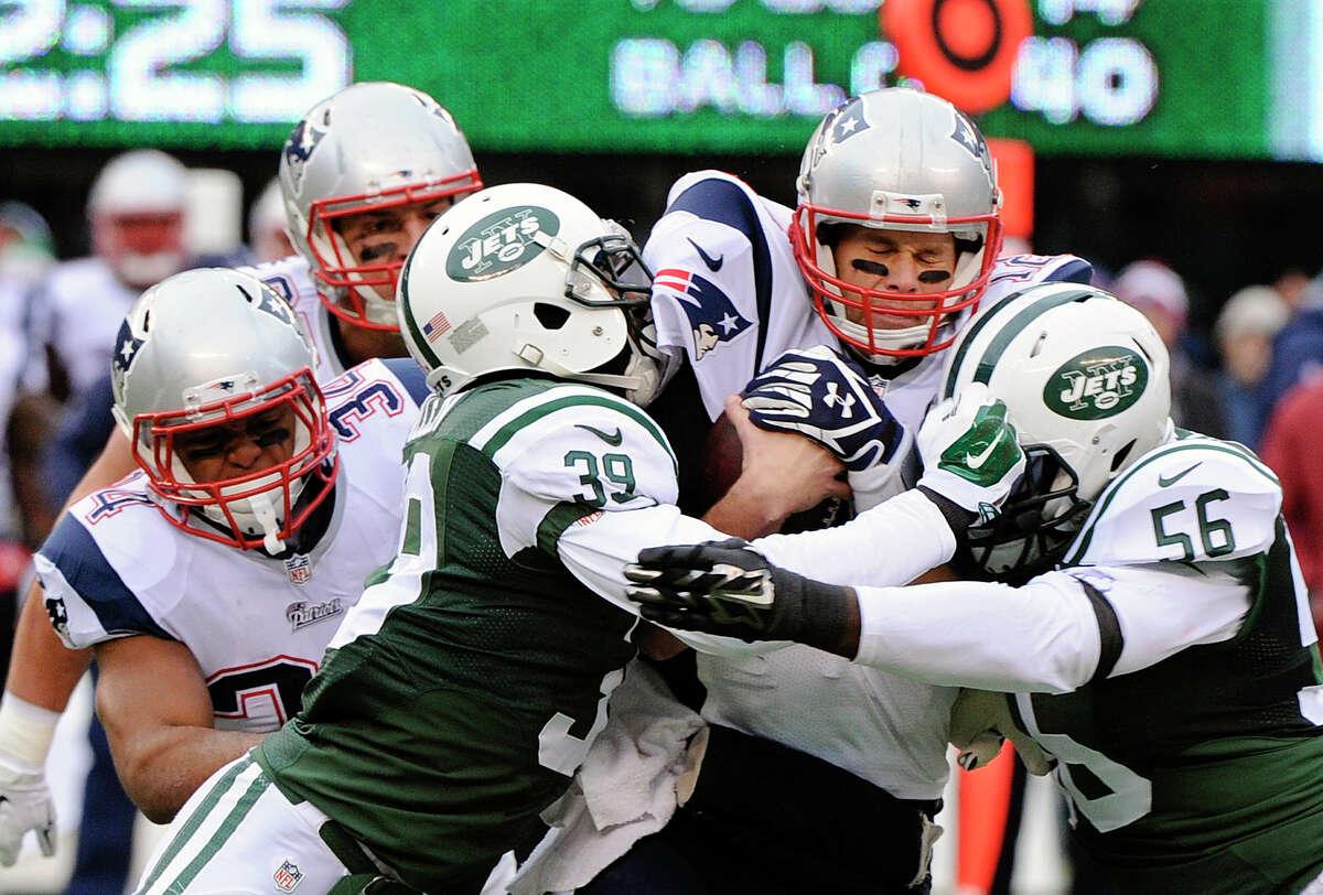 In this Dec. 21, 2014 file photo, New York Jets Antonio Allen (39) and Demario Davis (56) sack New England Patriots quarterback Tom Brady.