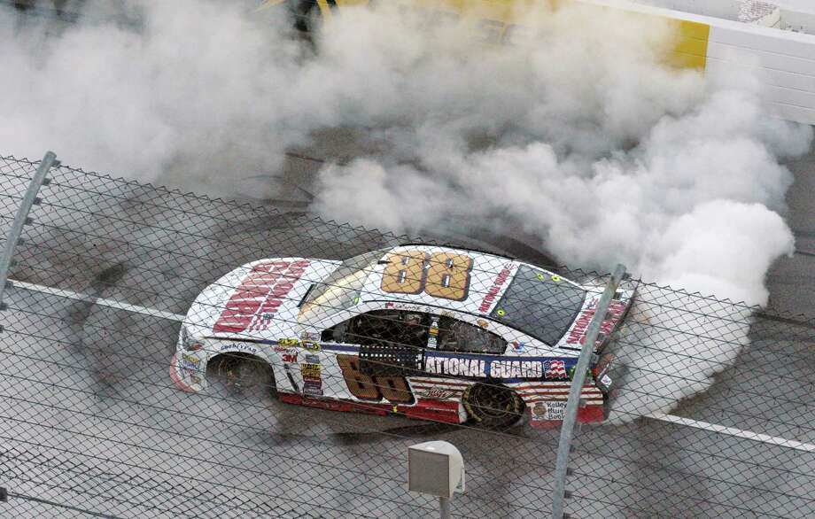 Dale Earnhardt Jr. does a burnout as he celebrates after winning at Martinsville Speedway on Sunday. Photo: Don Peterson — The Associated Press  / FRE 59093 AP