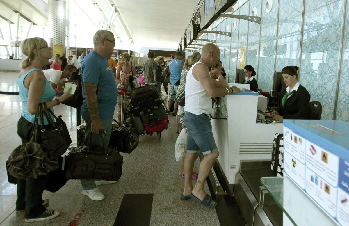 Tourists line up at a boarding desk as the leave Sousse, Tunisia, after the attack, Saturday June 27, 2015 at the Nfidha airport near Sousse. Tunisiaís prime minister announced on Saturday a string of new security measures including closing renegade mosques and calling up army reservists as thousands of tourists left the North African country in wake of its worst terrorist attack ever. (AP Photo/Salah Rhim)