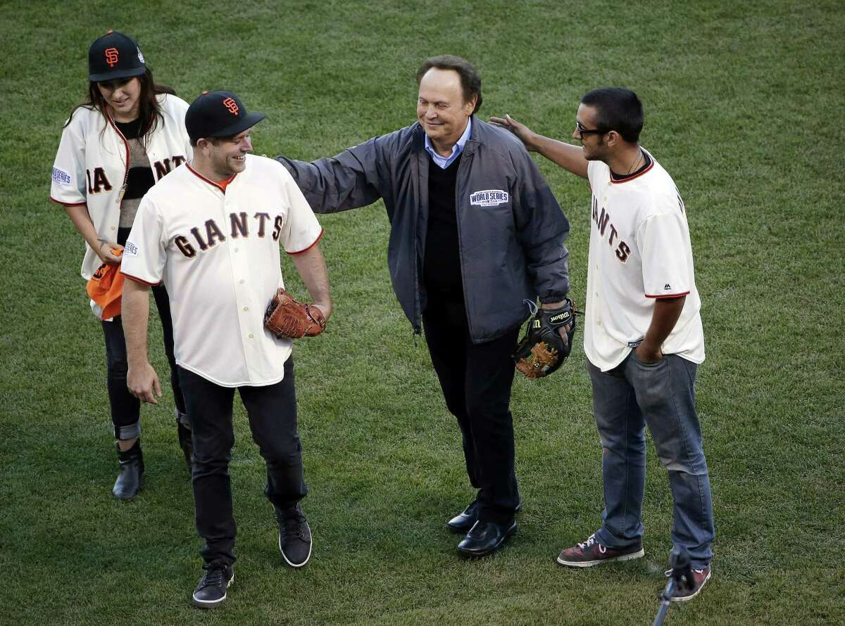 Robin Williams son, Zak Williams, second from left, gets a pat on the back from Billy Crystal after Zak threw out the ceremonial first pitch as his siblings Zelda, left, and Cody look on before Game 5 of the World Series on Sunday.