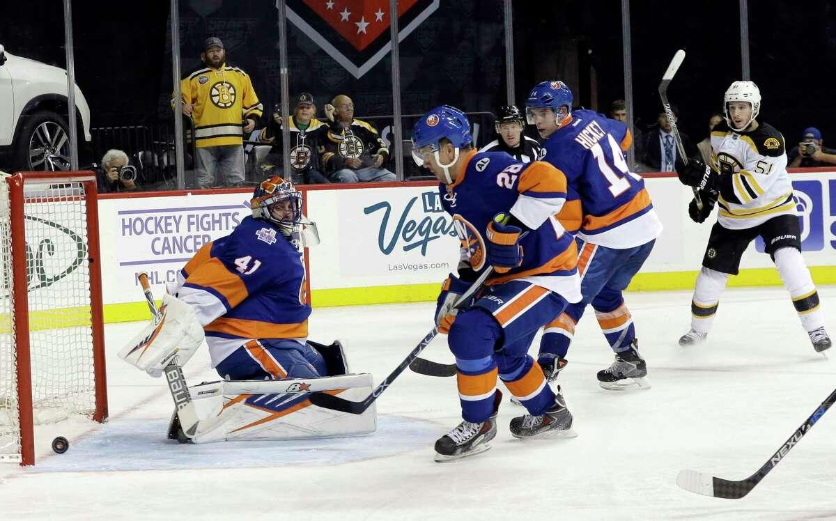 Boston Bruins center Ryan Spooner (51) scores a goal past Islanders goalie Jaroslav Halak (41), defenseman Marek Zidlicky (28) and defenseman Thomas Hickey (14) during the third period of Friday's game in New York.