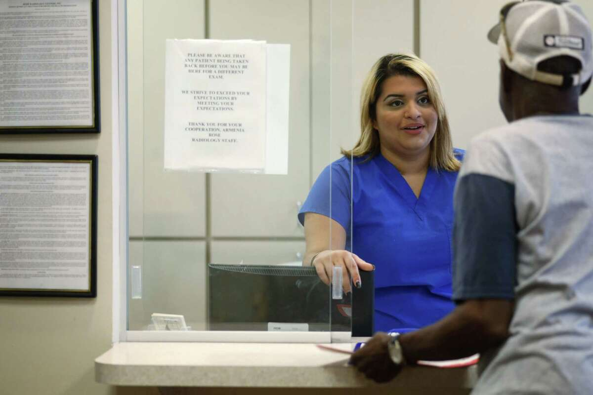 Lizzie Jimenez, 22, of Tampa, talks with a patient at Rose Radiology in Tampa, Fla., Thursday. Jimenez is a nursing student at St. Petersburg College and volunteered to help people sign up for the Affordable Care Act, and ended up getting herself coverage through the law. The Supreme Court sent a clear message Thursday that President Barack Obama's health care overhaul is here to stay, rejecting a major challenge that would have imperiled the landmark law and health insurance for millions of Americans.