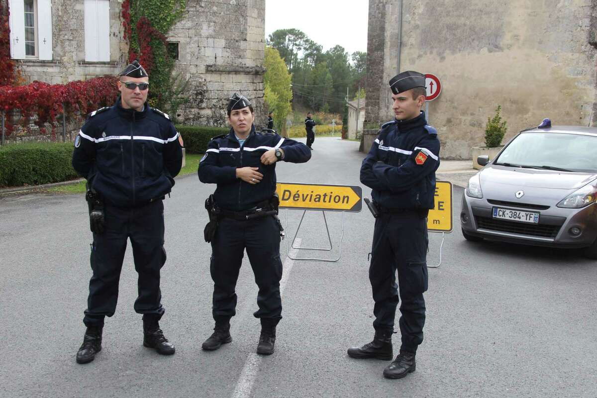 French gendarmes prevent access of a bus crash to the media in Puisseguin, near Bordeaux, southwestern France, following a road accident in which at least 42 people were killed, Friday, Oct. 23, 2015. A truck and a bus transporting retirees on a day trip collided and caught fire Friday on a country road in wine country in southwest France, killing 42 people and gravely injuring at least four others, authorities said.