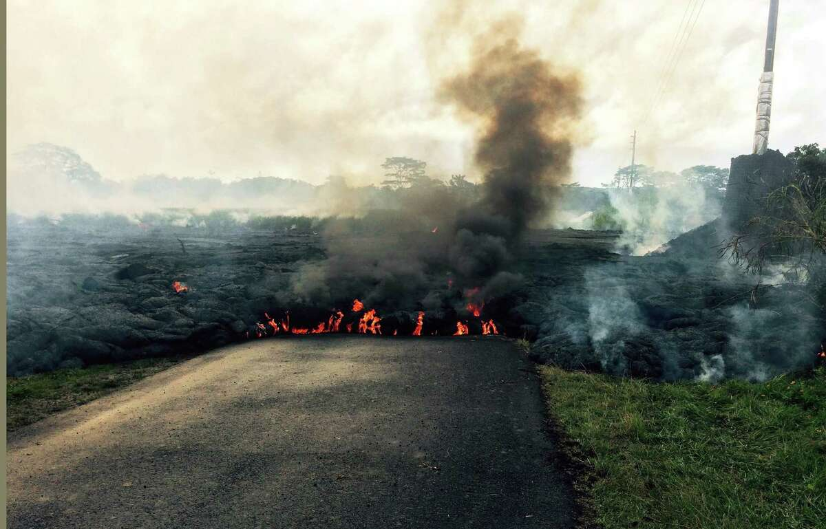 In this Oct. 24, 2014 photo from the U.S. Geological Survey, the lava flow from Kilauea Volcano that began June 27 is seen near the town of Pahoa on the Big Island of Hawaii. Authorities on Saturday told several dozen residents near the active lava flow to prepare for a possible evacuation in the next three to five days as molten rock oozed across the country road and edged closer to homes.
