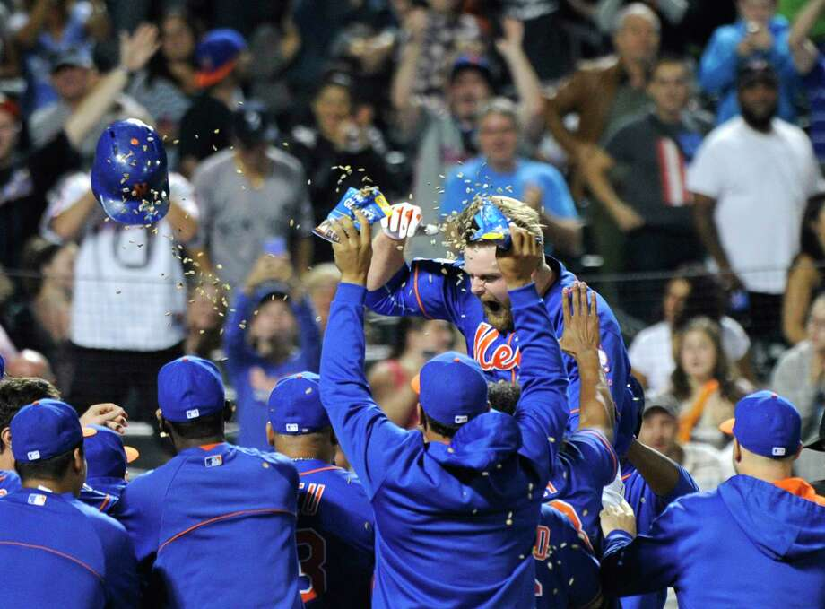 New York Mets first baseman Lucas Duda celebrates with his team after hitting a two-run walk-off home run against the Houston Astros last September. Photo: Bill Kostroun — The Associated Press File Photo  / FR51951 AP