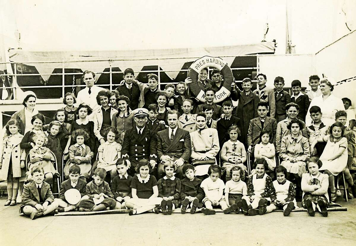 Eleanor and Gilbert Kraus and the captain of the ship, surrounded by their 50 rescued children.