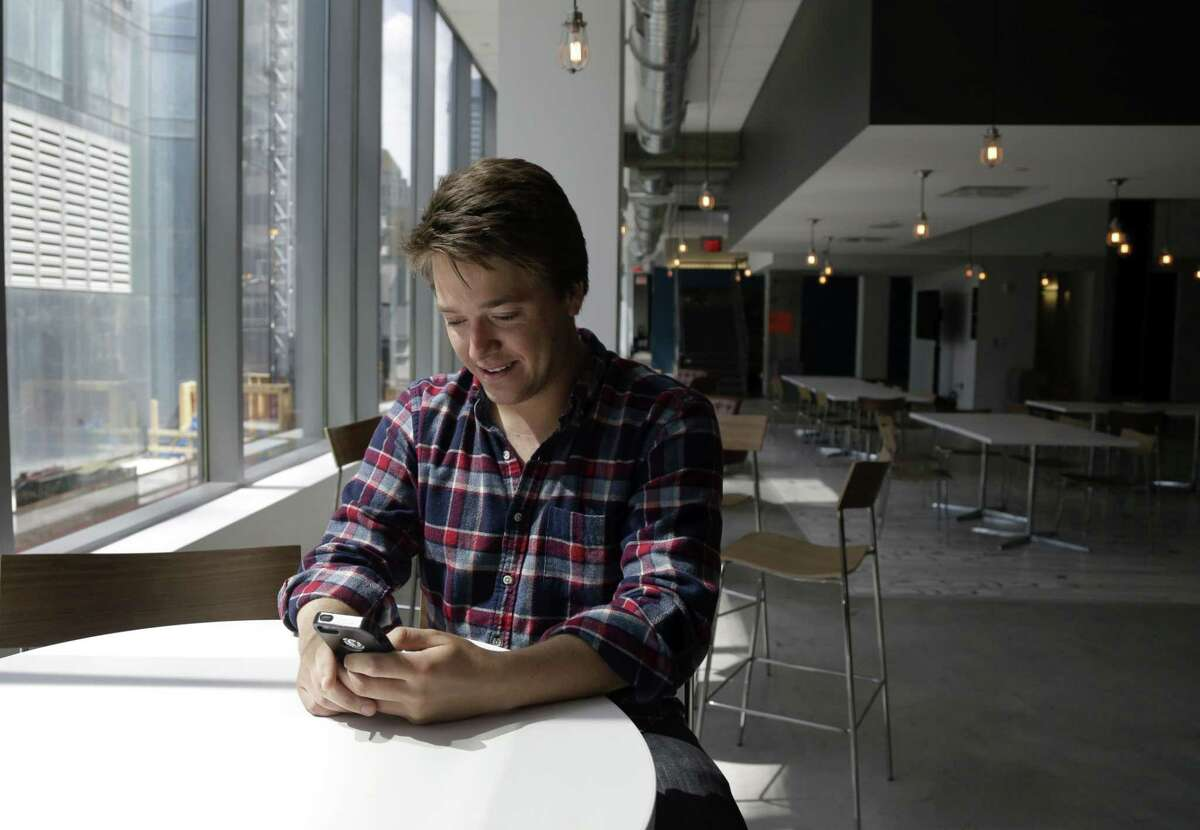 Alex Culbertson, 26, looks at his smartphone in his workplace cafe in Boston. On a recent trip to Maine with six friends, Culbertson had to split up a weekend tab of gas, hotel rooms, food and drink. One person paid for everything and they split the final result, via Venmo, the PayPal-owned app that lets users pay with a tap and a text-like message.