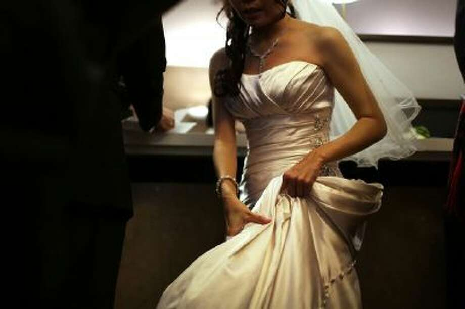 A bride waits to fill out marriage papers at a busy City Clerk's office in New York City.