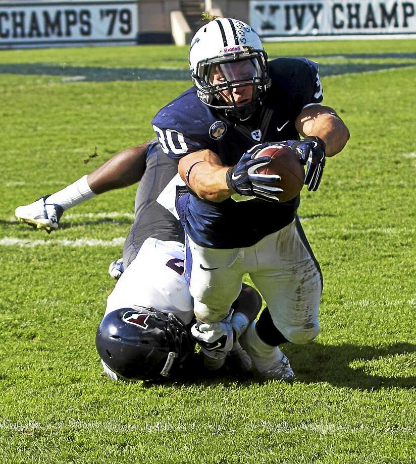 Yale running back Tyler Varga lunges for the Bulldogs' first touchdown on Saturday in their 43-21 win over Penn at Yale Bowl. Photo: Photo Courtesy Of Yale Athletics  / Steve Musco