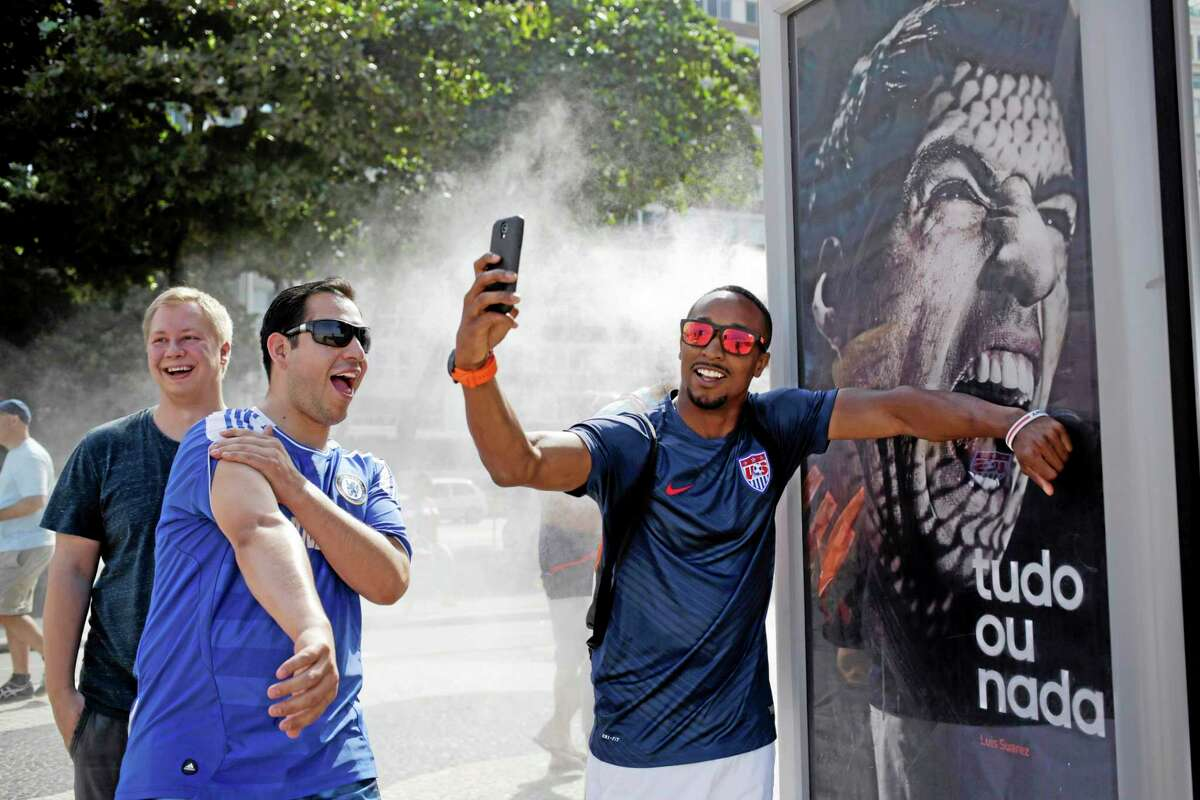 A U.S. soccer fan pretends Uruguay striker Luis Suarez is biting him as he takes a selfie Thursday next to an Adidas advertisement featuring Suarez near Copacabana beach in Rio de Janeiro, Brazil. FIFA banned Suarez from all football activities for four months on Thursday for biting an opponent at the World Cup, a punishment that rules him out of the rest of the tournament.