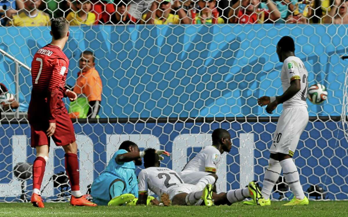 Portugal's Cristiano Ronaldo, left, scores his side's second goal during a group G World Cup match against Ghana Thursday at the Estadio Nacional in Brasilia, Brazil.