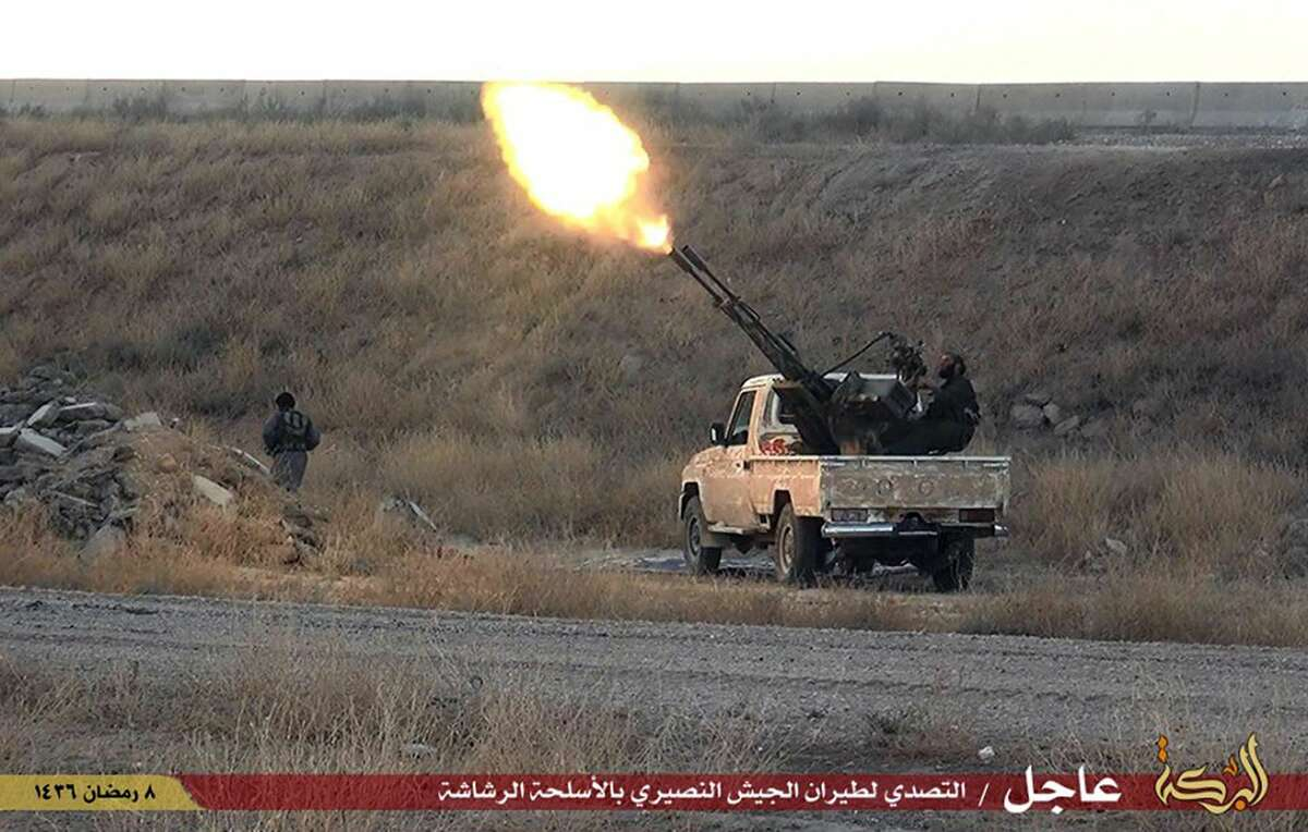 This photo provided by a website of the Islamic State group, taken Thursday, June 25, 2015, shows fighters of the Islamic State group opening fire toward Syrian warplane in the predominantly Kurdish Syrian city of Hassakeh, Syria. After weeks of setbacks, militants from the Islamic State group launched swift counteroffensives Thursday on predominantly Kurdish areas of northern Syria, killing and wounding dozens and setting off car bombs, activists and officials said. ( Islamic State militant website via AP)