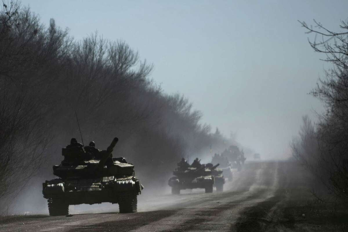 Ukrainian troops ride on tanks near Artemivsk, eastern Ukraine, Tuesday, Feb. 24, 2015. Ukrainian officials said they havenít yet started pulling heavy weapons back from a frontline in eastern Ukraine because of continued rebel violations of a cease-fire deal. (AP Photo/Evgeniy Maloletka)