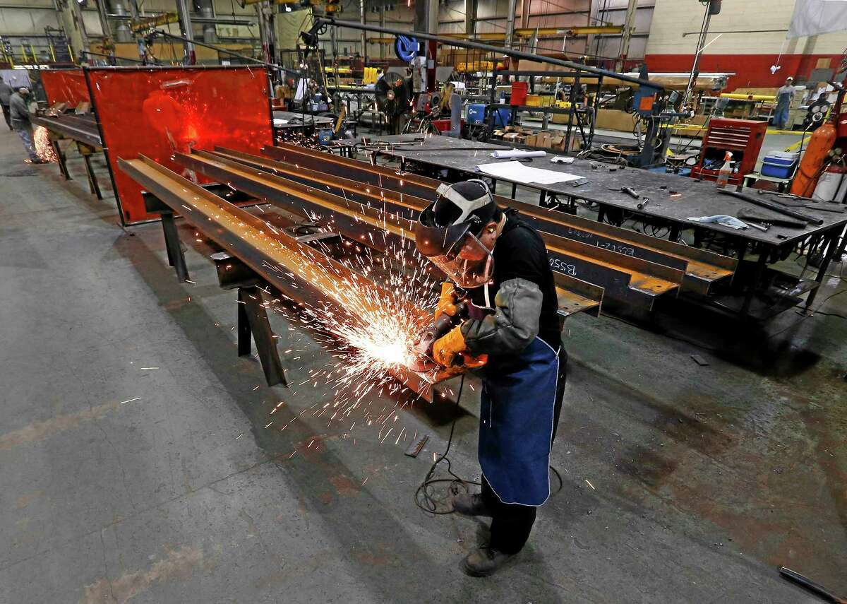 In this Thursday, Jan. 23, 2014 photo, Jesus Rodriguez grinds steel at the IDEAL Group in Detroit. The Institute for Supply Management reports on U.S. manufacturing activity in February on Monday, March 3, 2014.