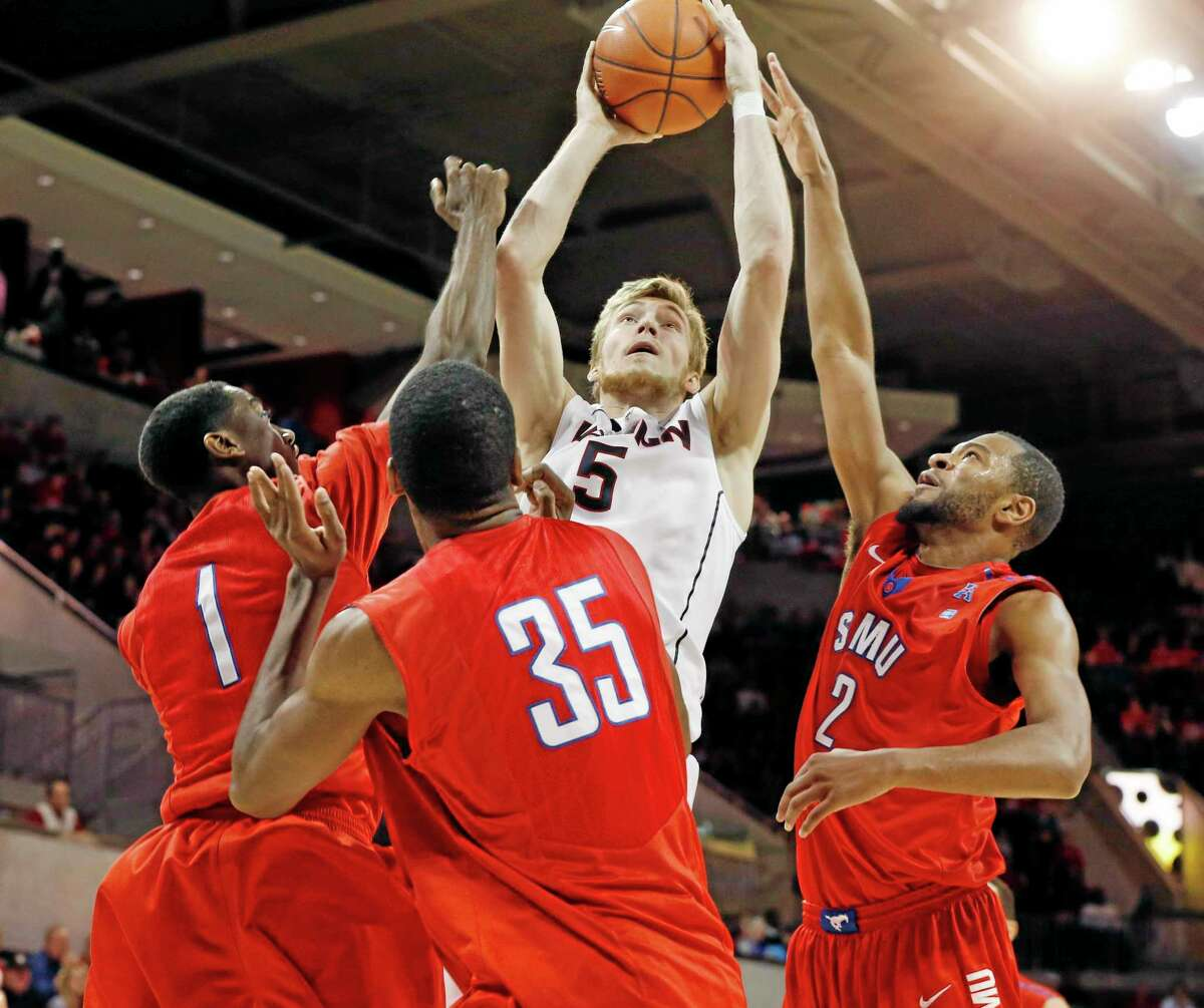 SMU guard Ryan Manuel (1), center Yanick Moreira (35) and forward Shawn Williams (2) defend UConn's Niels Giffey during the second half of the Mustangs' 74-65 win on Saturday in Dallas. The Huskies look to get back on track against Harvard Wednesday night.
