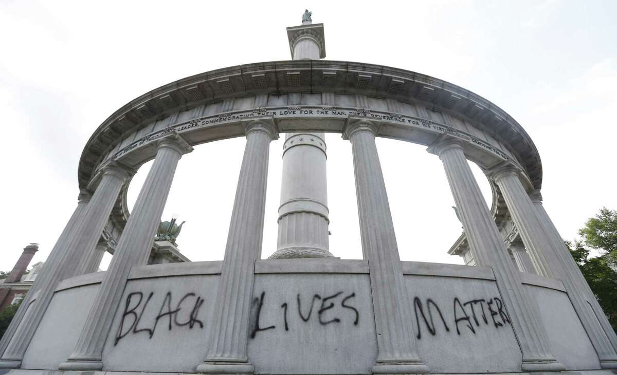 FILE - This June 25, 2015, file photo shows the words ìBlack Lives Matterî spray painted on a monument to former Confederate President Jefferson Davis in Richmond, Va. Confederate monuments in a half-dozen places this week have been defaced _ a telling sign of the racial tension that permeates post-Ferguson America. (AP Photo/Steve Helber, File)